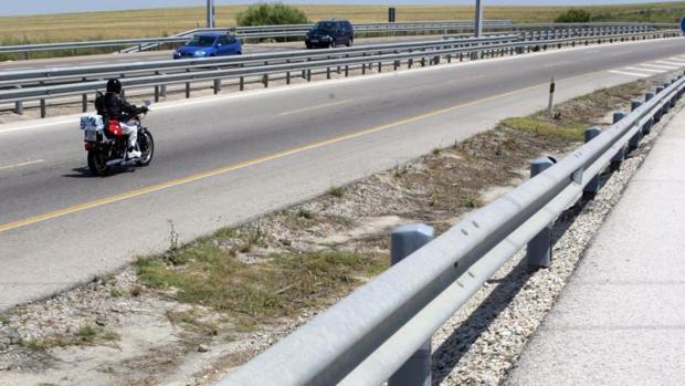 Un motorista circula por una carretera con barreras quitamiedos