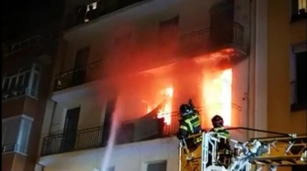 Los bomberos tratan de extinguir las llamas del incendio que rompe por la fachada