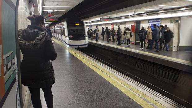 Viajeros esperan la llegada del Metro en una estación madrileña
