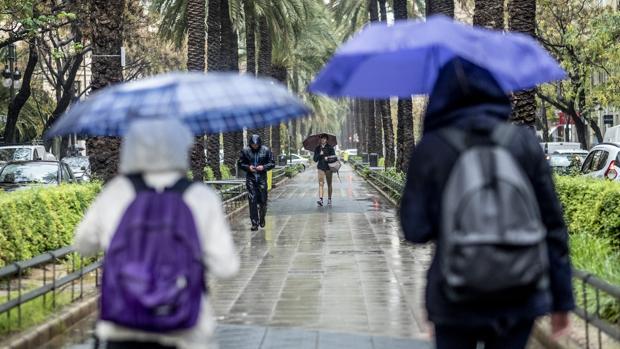 Unos jóvenes se protegen de la lluvia en Valencia