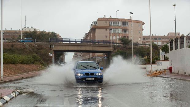 Un vehículo circula esta mañana por una calle inundada en la zona del Parque de las Naciones de Torrevieja (Alicante)