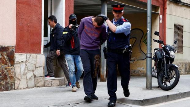 Los Mossos conducen al detenido tras el registro de su vivienda en Cornellá