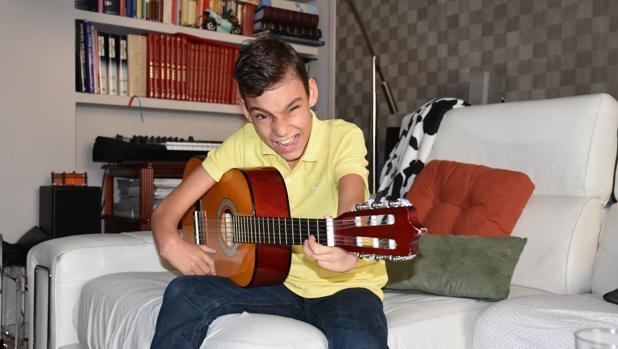 Adrián en el salón de su casa con su guitarra