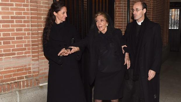 De luto riguroso y mantiña, arropada por su hija y el sacerdote a la salida del funeral