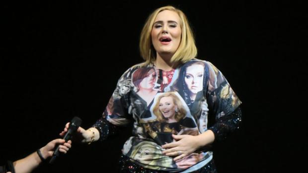 Adele se coloca emocionada una sudadera que le regala una de sus fans