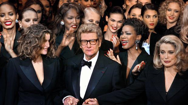 Yves Saint Lauren, flanqueado por las modelos Laetitia Casta y Mounia