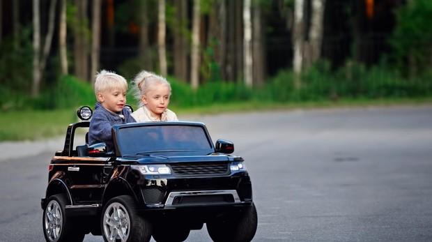 Dos niños, en un coche eléctrico.