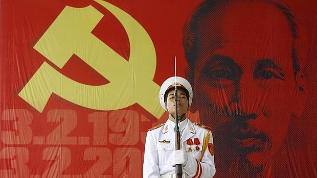 Un militar sostiene un rifle ante una imagen del líder comunista vietnamita Ho Chi Minh