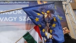 Un miembro del partido de extrema derecha húngaro Jobbic quema una badera de la UE, como muestra de su euroescepticismo