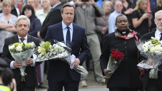 El primer ministro David Cameron (2i), presidente de la Cámara de los Comunes británica, John Bercow (i) y el líder laborista Jeremy Corbyn llevan flores al altar improvisado de Jo Cox
