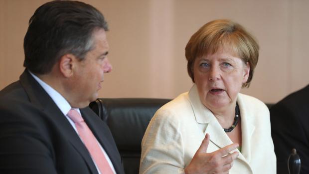La canciller alemana, Angela Merkel y el ministro alemán de Economía, Sigmar Gabriel hablan hoy martes antes del inicio de la reunión del Consejo de Ministros en Berlín