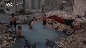 El ingenio de la guerra: niños sirios utilizan como piscina el cráter de una bomba