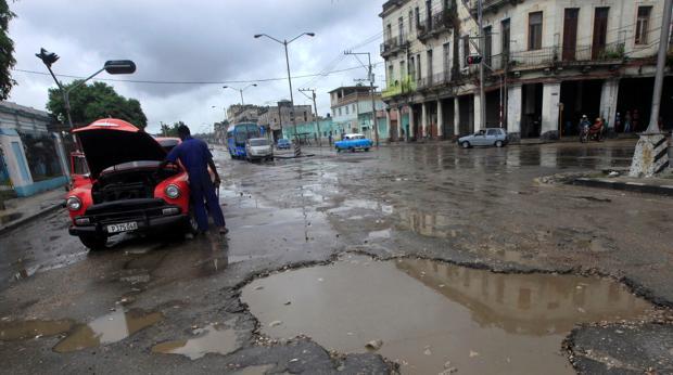 Un hombre intenta reparar su vehículo en una calle de La Habana mientras llueve