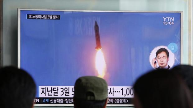 Varias personas prestan atención a un informativo en Seúl (Corea del Sur) en el que se informa del lanzamiento, por parte de Corea del Norte, de tres misiles balísticos al Mar de Japón