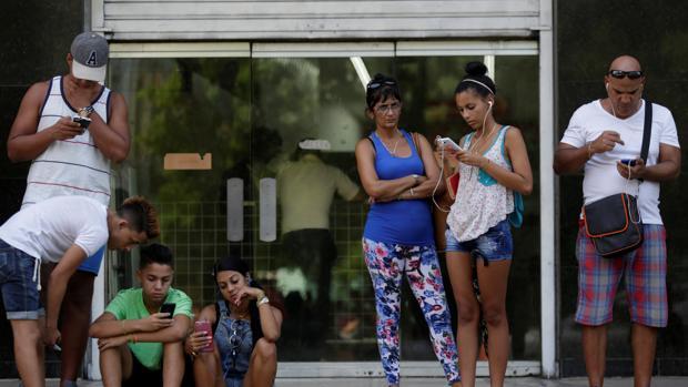 Ciudadanos cubanos usando sus teléfonos móviles