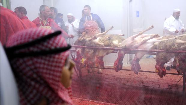Niños miran a través de una ventana cómo se trabaja en una carnicería de Marsella durate la Fiesta del Cordero