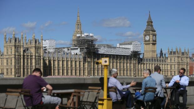 Personas sentadas en una terraza junto al Támesis desde la que se puede observar el Parlamento británico, en obras