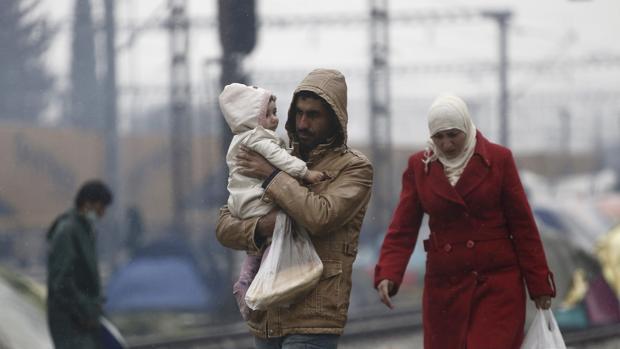 Una familia de refugiados espera cerca de Idomeni (Grecia) para cruzar la frontera con Macedonia
