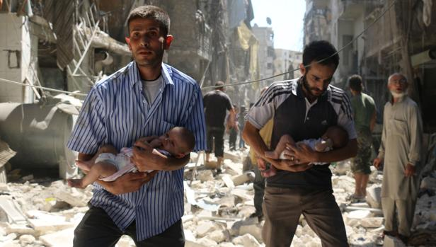 Dos hombres sirios protegen a dos bebés en el bombardeado barrio rebelde de Salihin, este domingo en Alepo (norte de Siria)