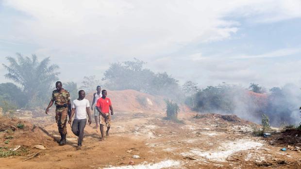 Varias personas, entre ellas un policía, abandonan el vertedero en que se produjo una explosión el viernes pasado en Benín