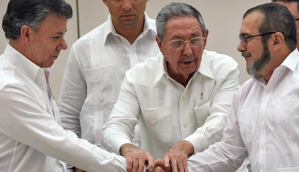 Juan Manuel Santos (i) y el líder de las FARC Timochenko (d) se saludan en presencia de Raúl Castro en septiembre de 2015 en La Habana