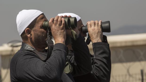Dos hombres observan con prismáticos, desde la parte siria, los Altos del Golán, donde tienen lugar las escaramuzas de los Ejércitos sirio e isrelí