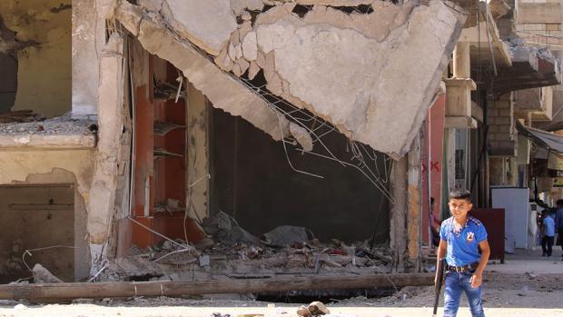 Un niño con una arma de jugete pasa junto a un edificio en ruinas en la ciudad siria de Qamishli el pasado 13 de septiembre, dos días después de que se decretase una tregua