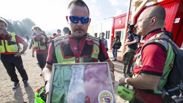 Un voluntario sujeta la antigua bandera de Amatrice recuperada por los servicios de rescate delante de un improvisado colegio en Amatrice
