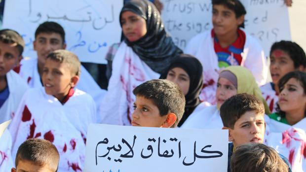 Un grupo de niños de un barrio de Alepo controlado por los rebeldes pide la entrada de ayuda