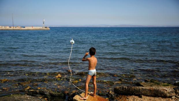 Un niño sirio juega junto al mar en el campo de refugiados de Souda, en la isla griega de Quíos