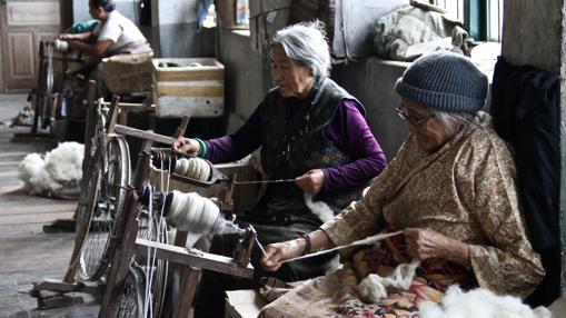 Dolma y Sangmo, dos ancianas que huyeron del régimen chino en 1959, tejen lana en un taller del Centro de Autoayuda para Refugiados Tibetanos de Darjeeling.