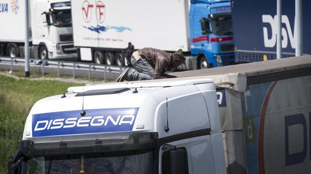 Un inmigrante se encarama a un camión que se dirige al túnel del Canal de la Mancha en dirección al Reino Unido en el puerto de Calais el 25 de junio de 2015