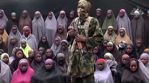 Imagen difundida el pasado mes de agosto por Boko Haram, en la que se observa, junto al yihadista, a un grupo de las estudiantes de Chibok secuestradas en 2014