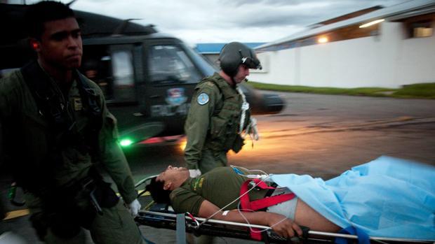 Soldados colombianos trasladan a un compañero que cayó en un campo minado en el departamento de Antioquia, noroeste del país