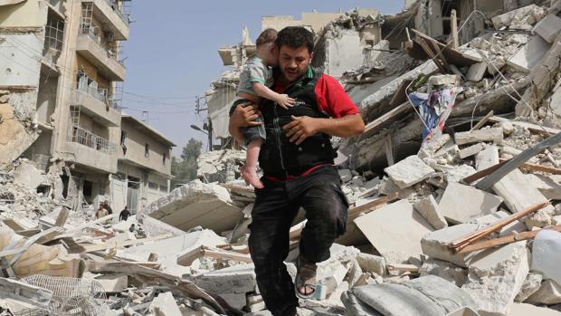 Un hombre huye con un niño de los escombros provocados por los bombardeos en Alepo
