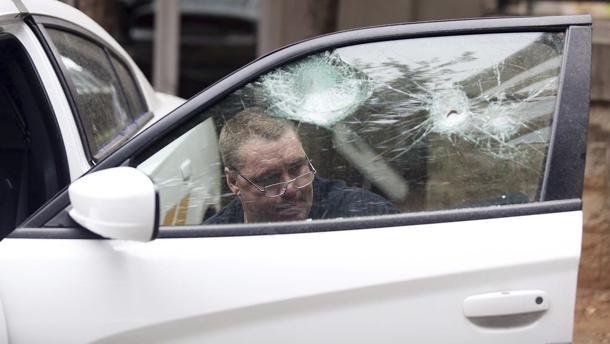 Un hombre arregla la ventana de uno de los coches patrulla dañados durante la protestas de Charlotte