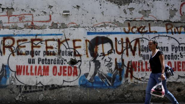 Una venezolana pasa por un mural del desaparecido presidente Hugo Chávez, sobre el que se reclama la celebración de un referéndum revocatorio de Maduro, este jueves en Caracas