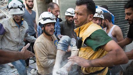 Miembros de los equipos de rescate conocidos como «Cascos blancos» trasladan a un herido recuperado de los escombros que causó el bombardeo sobre un distrito rebelde de Alepo