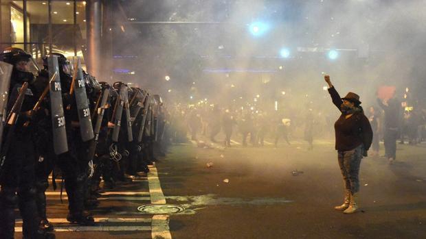 Manifestantes se encaran a policías antidisturbios con los brazos en alto durante unos disturbios en Charlotte en Carolina del Norte