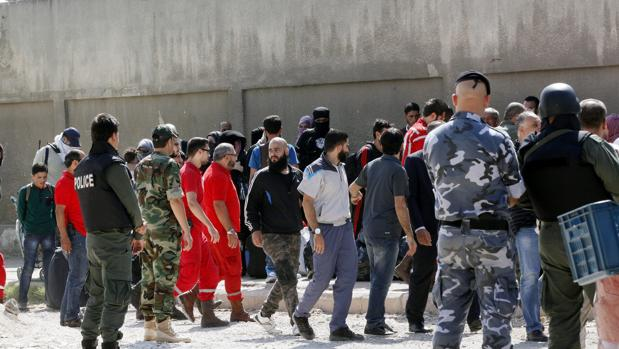 Soldados y Voluntarios de la Media Luna Roja Siria ayudan a rebeldes y familiares durante la evacuación del barrio asediado de Al Waer, en la ciudad de Homs