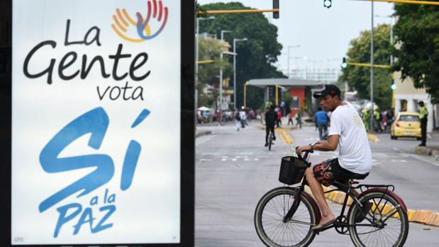 Un hombre pasa con su bicicleta cerca de un cartel a favor del «sí» a los acuerdos de paz, en Cartagena de Indias