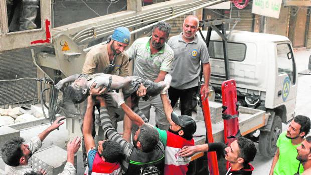 Un equipo de rescate recupera el cuerpo de un niño sirio tras un ataque