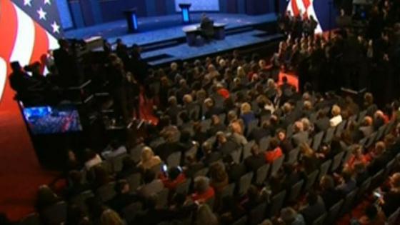 Los candidatos se retrasan. El público se mantiene expectante.