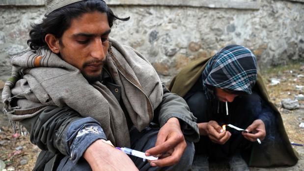 Drogadictos afganos inyectándose y fumando heroína