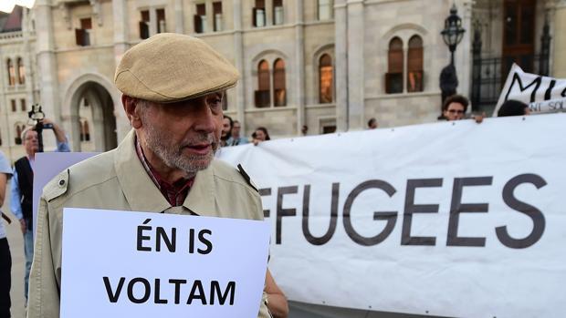 Un hombre sostiene un cartel que reza: «Yo también fui refugiado» en Hungría