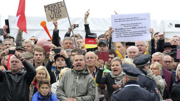 Manifestantes piden la renuncia de la canciller Merkel, durante la fiesta de la unidad alemana, este lunes en Dresde