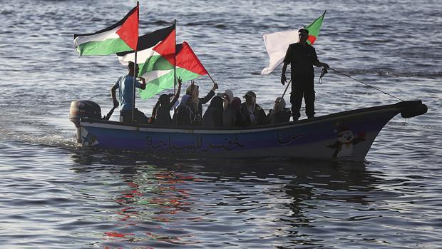 Varias mujeres palestinas ondean su bandera nacional en solidaridad con la coalición Flotilla de la Libertad cerca del puerto de Gaza