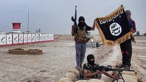 Foto de archivo de combatientes de Daesh muestran una bandera de la organización terrorista