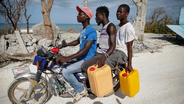 Tres Haitianos portan agua a bordo de una motocicleta frente a las ruinas de una casa derribada por «Matthew»