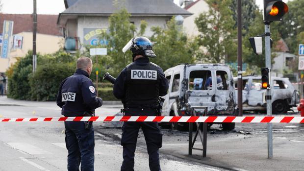 Vehículo polícial y furgoneta incendiados por cócteles Molotov lanzados por una quincena de individuos, este sábado en Viry-Chatillon, cerca de París
